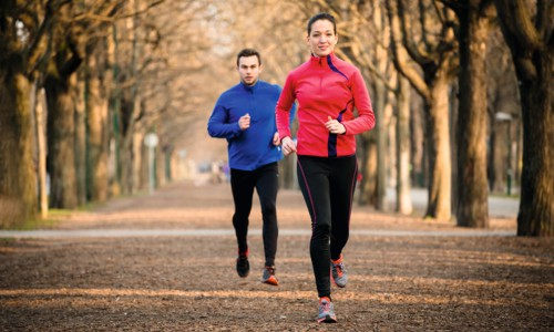 E1B5XG Jogging couple - young man and woman competing, woman first